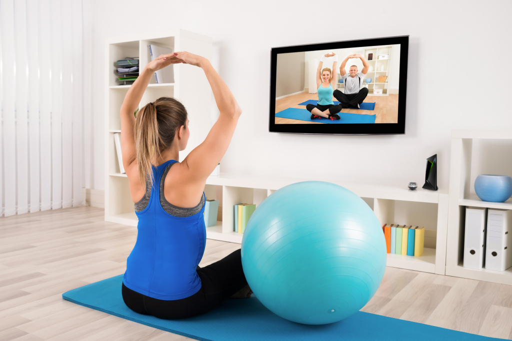 Pregnant Woman Doing Yoga By Watching Television