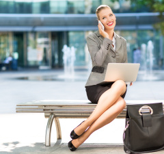 Businesswoman using laptop outdoors
