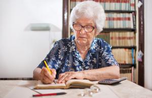 Senior woman calculating budget at home.
